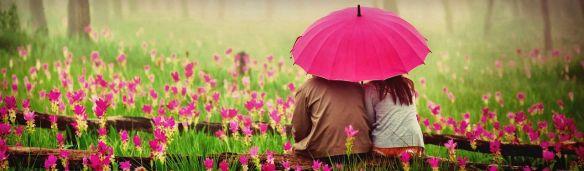 cute-couple-with-umbrella-in-blossom-field-web-header